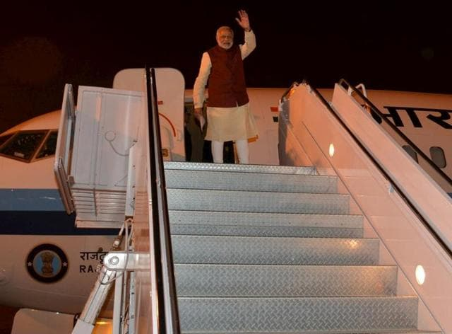 Prime Minister Narendra Modi waves from the plane after meeting with his Pakistani counterpart Nawaz Sharif in Lahore.