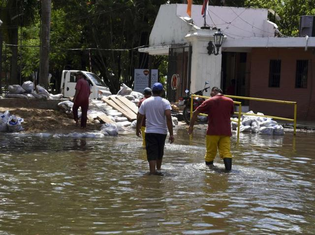 Locals recover belongings from a flooded neighbourhood in Asuncion on December 24, 2015. Constant and heavy rains in the country have caused the overflowing of the Paraguay river, forcing 150,000 to evacuate.