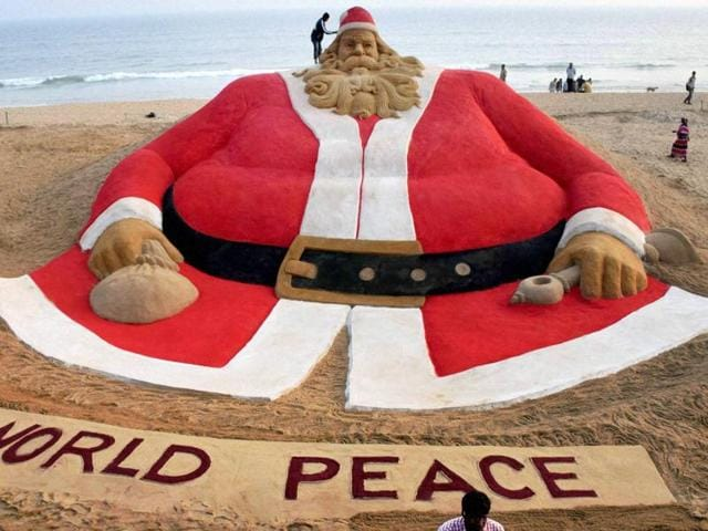 "Sand artist Sudarsan Pattnaik creates a 45ft high sand Santa Claus with message ""World Peace"