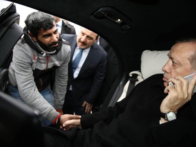 Turkish President Recep Tayyip Erdogan (R) shakes hands with a man who was allegedly about to attempt suicide off the Bosporus bridge in Istanbul.