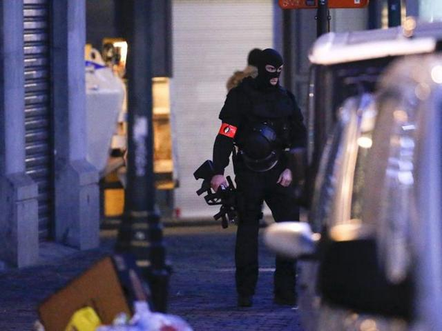 A Belgian special forces police officer patrols a street during a police raid in central Brussels.