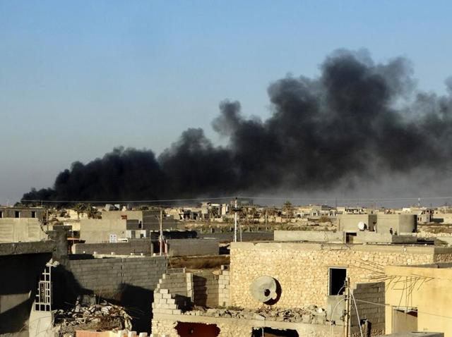In this Friday, Dec. 25, 2015 photo, smoke rises from Islamic State positions following a US-led coalition airstrike as Iraqi Security forces advance their position in downtown Ramadi.