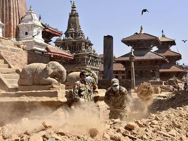 Nepalese army personnel clear earthquake debris in Patan Durbar Square complex in Kathmandu, Nepal.