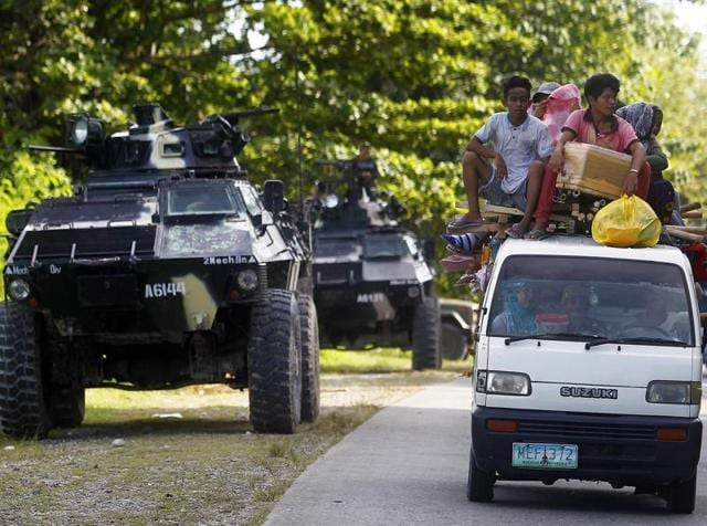 People drive past an armoured personnel carrier (APC) in Kauran, Ampatuan in the southern Philippines province of Maguindanao.Fourteen were killed, including nine Christian villagers, by Bangsamoro Islamic Freedom Fighter insurgents, while at least five rebels killed by government forces in clashes.
