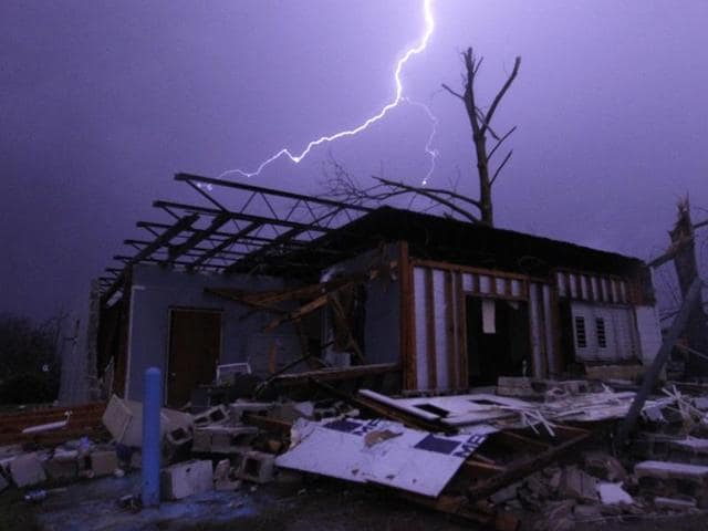 Lightning illuminates a house after a tornado touched down damaging several houses, Friday, December 25, 2015, in Birmingham, Alabama.