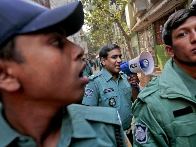 Bangladeshi police officials secure the area during a raid on a building where members of a banned Islamist group were detained with bombs in Mirpur area, Dhaka.