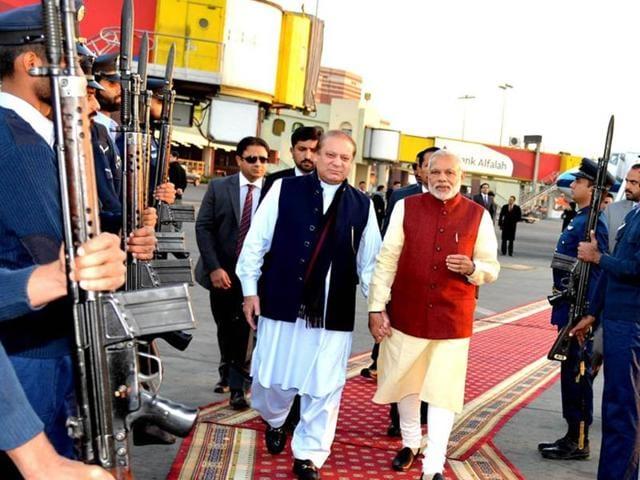 Pakistani Prime Minister Nawaz Sharif (L) walks with his Indian counterpart Narendra Modi after Modi's arrival in Lahore, Pakistan, December 25, 2015.