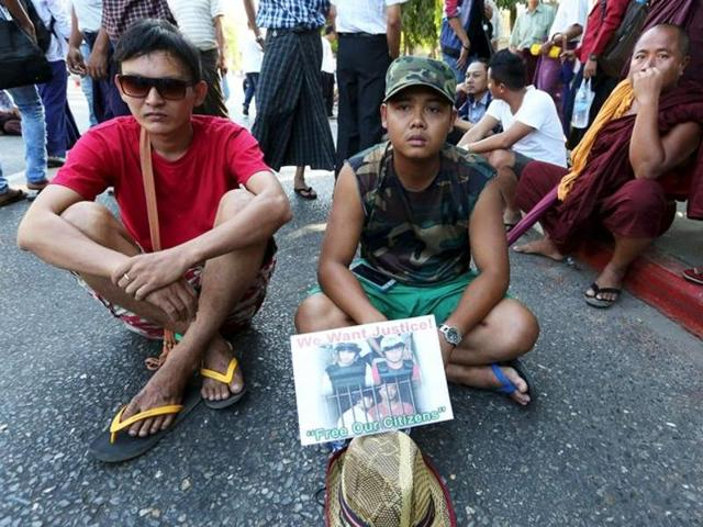 Protesters sit on the road as they protest in support of two Myanmar migrant workers Zaw Lin and Win Zaw Htun in front of the Thai embassy in Yangon December 25, 2015.(REUTERS)
