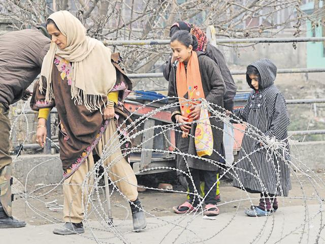 A Kashmiri Muslim woman crosses the barbed wire set up as barricade by police to enforce restrictions in Maisuma area of Srinagar.