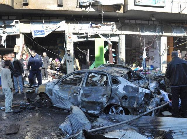 Syrian citizens gather at the scene where twin bombs attack a street, at the government-held neighbourhood of Zahraa, in Homs province.