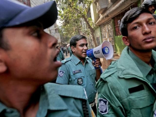 Bangladeshi police officials secure the area during a raid on a building where members of a banned Islamist group were detained. Two suspected militants were killed in an explosion outside the capital of Dhaka after security forces continued to conduct raids against extremist hideouts.