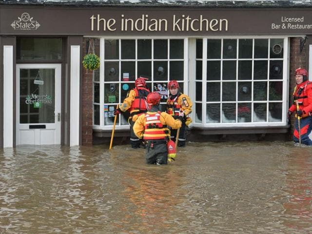 Members of the Mountain Rescue team stand over kneed deep in water outside a property, after floods, in Tower Street, York.