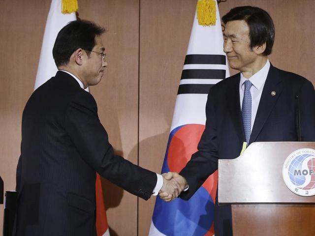 South Korean foreign minister Yun Byung-se, right, shakes hands with his Japanese counterpart Fumio Kishida after their joint press conference at Foreign Ministry in Seoul, South Korea.