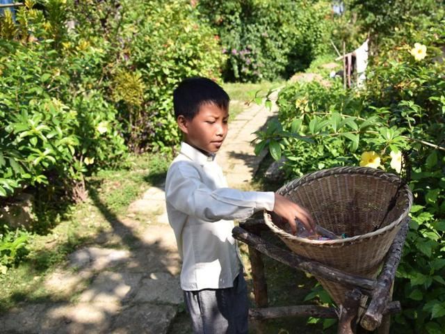 Rubbish is thrown into a pit dug near the village where it is left to turn into compost and plastic bags are banned, says BBC. A child uses a bamboo dustbin placed beside a road in Mawlynnong, Meghalaya. (AFP)
