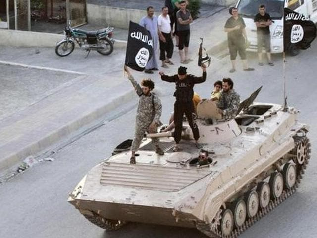 """Militant Islamist fighters hold the flag of Islamic State (IS) while taking part in a military parade along the streets of northern Raqqa province in this June 30, 2014 file photo.  IS has set up departments to handle """"war spoils,""""  creating the trappings of government that enable it to"""