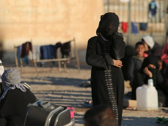 Displaced women, fleeing violence in Aleppo city and from Islamic State-controlled areas in Raqqa and Deir al-Zor, wait at a school in al-Mabroukeh village in the western countryside of Ras al-Ain, Syria December 28, 2015.