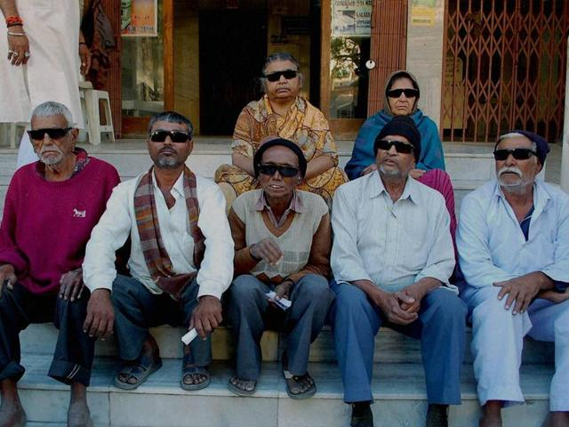 Seven patients sitting outside the Sadhu Vaswani hospital in Rajkot where they lost their vision after retina operation on Monday.