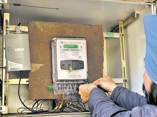 A PSPCL employee installing a smart electricity meter in Jalandhar on Monday.