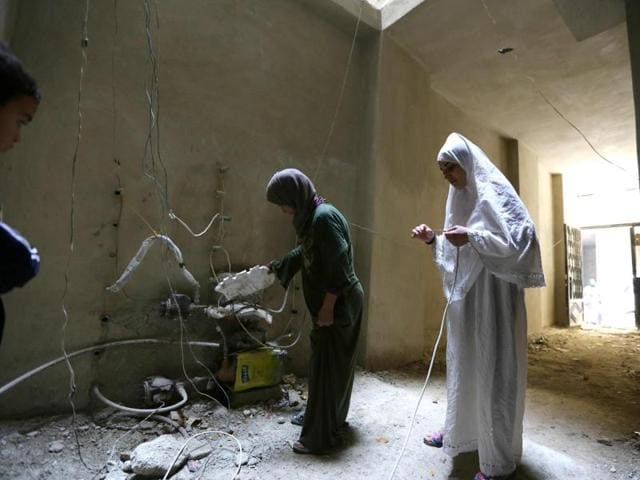 Relatives of Syrian Umm Walid check wires in an unfinished building where the family lives in the Daf al-Sakhr neighbourhood of Jaramana on the outskirts of the Syrian capital Damascus.