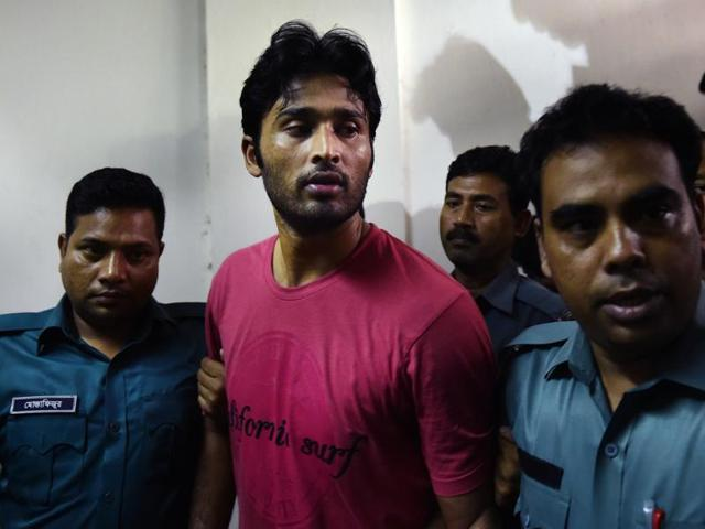 Bangladeshi cricketer Shahadat Hossain is taken away by policemen after he surrendered before a court in Dhaka.