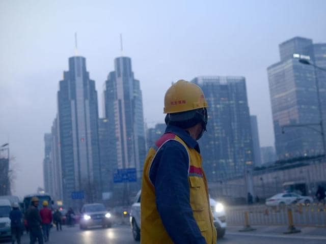 """A Chinese worker walks along a street after work in Beijing. Construction workers, machine operators in factories, office cleaners have been denied, and their children have long been denied equal access to public services such as schools, hospitals and housing under a decades-old household registration system known as """"hukou""""."""