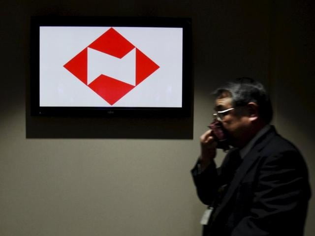 A man walks past a logo of Japanese life insurer Nippon Life at the company's headquarters in Tokyo.