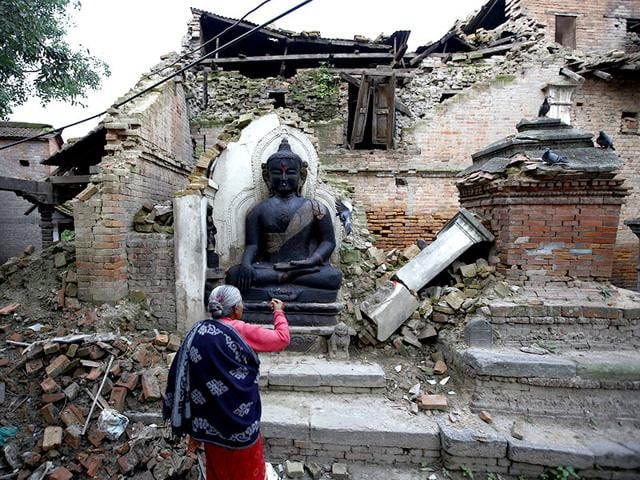 A woman offers daily prayers at the statue of Lord Buddha that was damaged during the earthquake in Bhaktapur. Earthquake survivors in Nepal are still in a dire need for food, shelter and clean water.