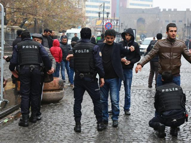 Police officers search civilians as they enter Sur district, which is partially under curfew, in the southeastern city of Diyarbakir, Turkey.