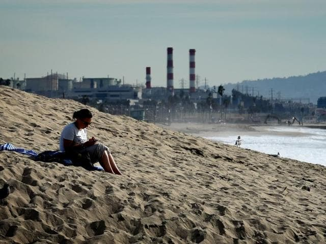 A woman sits on a sand berm created by city workers to protect houses from El Nino storms and high tides in Los Angeles. After the world leaders reached the first truly universal climate pact, aimed at limiting average global warming to two degrees Celsius, the hard part now comes– following up on all the commitments.