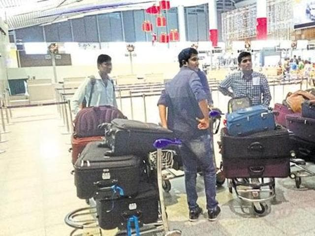 A group of students wait after being stopped at the Rajiv Gandhi International Airport in Hyderabad from boarding a US-bound flight on December 22.