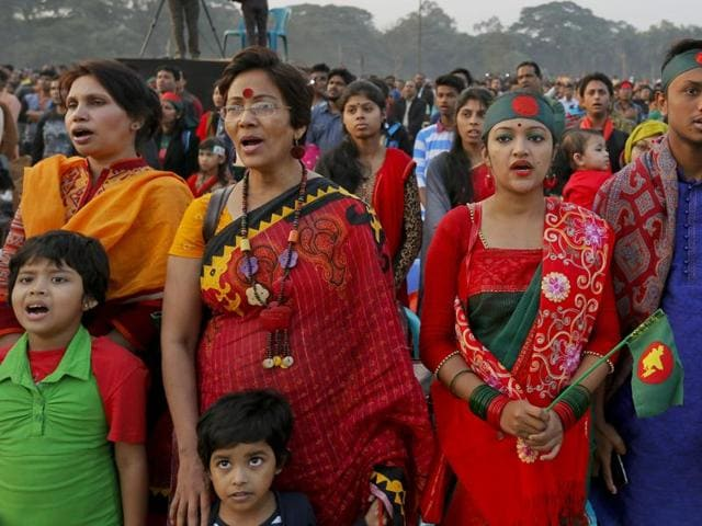 Bangladeshi people sing their national anthem as they mark the moment when the Pakistan army surrendered at this place on this day in 1971, in Dhaka, Bangladesh