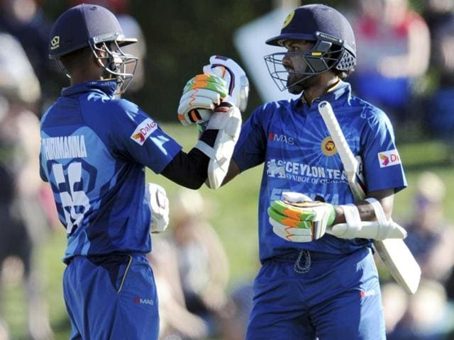 Tillakaratne Dilshan (R) of Sri Lanka plays a shot in front of New Zealand wicketkeeper Luke Ronchi during the third ODI at Saxton Oval in Nelson on December 31, 2015.