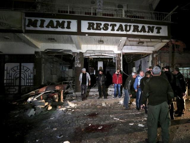 Residents inspect damage from a suicide bomb in Qamishli in Syria. Twin suicide bombings hit two restaurants in the Kurdish-controlled city in northeastern Syria on Wednesday, killing or wounding dozens of people, a Kurdish official and a group monitoring the war said.