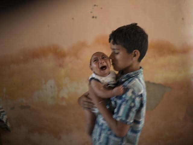 In this Dec. 23, 2015 photo, 10-year-old Elison nurses his 2-month-old brother Jose Wesley at their house in Poco Fundo, Pernambuco state, Brazil.
