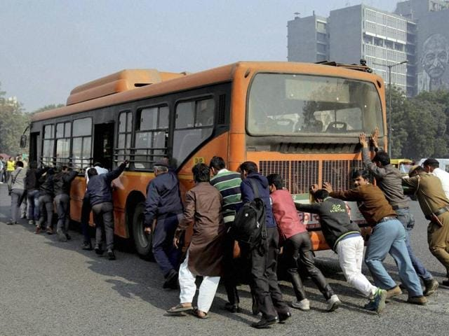 Passengers and traffic policemen push a bus after it broke down at a traffic intersection on the first day of odd-even scheme to fight pollution in New Delhi on Friday.