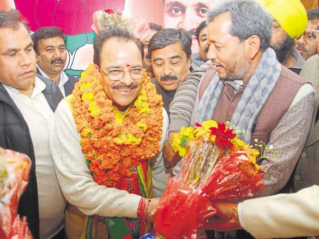 BJP state ex-president Tirath Singh Rawat presents a bouquet to newly elected state chief Ajay Bhatt (in garland).
