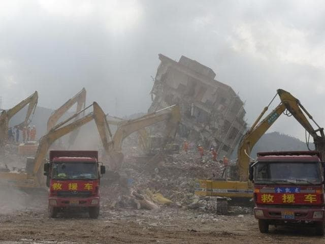 Rescuers walk among the debris of collapsed buildings as excavators and trucks work at the site of a landslide which hit an industrial park on Sunday, in Shenzhen, Guangdong province.