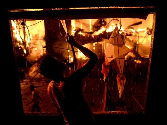 A resident jumps as a fire engulfs houses at a poor neighborhood of Tondo in Manila.