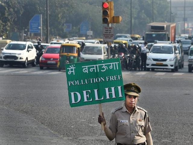A civil defence volunteer holds a placard during a trial run of the odd-even car scheme at ITO in New Delhi.
