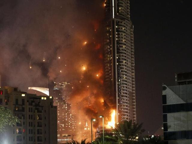 Smoke billows from the Address Downtown Hotel, after it caught on fire hours earlier, past fireworks, near the Burj Khalifa.