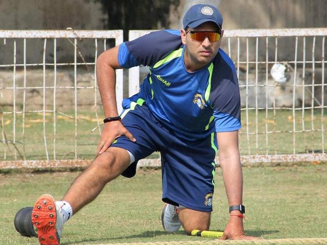 Yuvraj Singh stretches himself as he waits for his turn to bat during Ranji Trophy match against Madhya Pradesh.