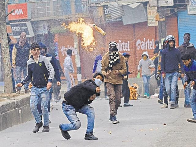 A Kashmiri protester throws petrol bombs at Indian policemen during a protest in Srinagar on Friday. Police fired tear gas and rubber bullets to disperse protesters demanding the disbanding of village defence committee, a body of civilian volunteers armed by the government to fight insurgents, after their members allegedly killed three people recently, including a woman and her four-year-old son.