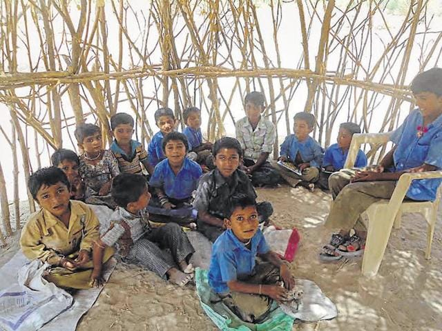 Children sit on ground inside a ramshackle structure while attending classes in a remote border area of Rajasthan.