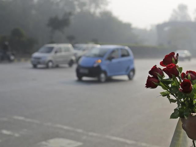 A civilian volunteer holds roses to be given to the drivers not following the rules on the first day of a two-week experiment to reduce the number of cars to fight pollution in New Delhi.