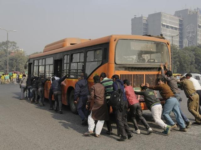 Passengers and traffic policemen push a bus after it broke down at a traffic intersection on the first day of a two-week experiment to reduce the number of cars to fight pollution in New Delhi.