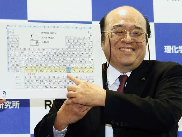 Kosuke Morita of Riken Nishina Center for Accelerator-Based Science points at periodic table of the elements during a press conference in Wako, Saitama prefecture, near Tokyo Thursday, Dec. 31, 2015.