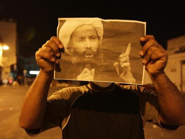 In this Wednesday, Oct. 15, 2014, file photo, a Bahraini anti-government protester holds up a picture of jailed Saudi Sheik Nimr al-Nimr during clashes with riot police in Sanabis, Bahrain, a suburb of the capital Manama.