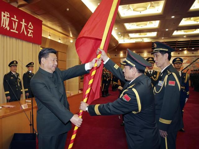 In this December 31, 2015 photo released by China's Xinhua News Agency, Chinese President Xi Jinping, front left, gives a military flag to Wei Fenghe, front center, commander of the Rocket Force of the Chinese People's Liberation Army (PLA), and Wang Jiasheng, front right, political commissar of the Rocket Force, in Beijing.