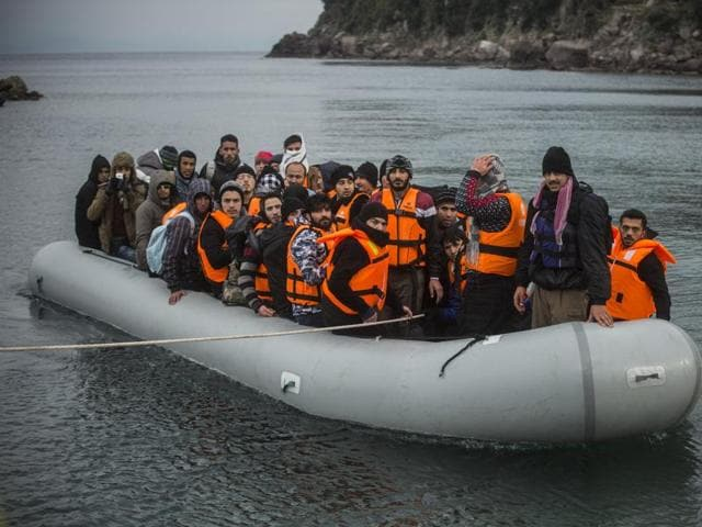 Refugees and migrants onboard a dinghy arrive at the village of Skala, on the Greek island of Lesbos, after crossing the Aegean sea from Turkey, Saturday, Jan. 2, 2016.