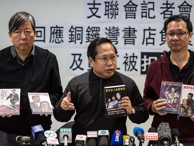 Pro-democracy group members Lee Cheuk Yan (2nd L), Albert Ho (C) and Richard Tsoi (4th L) hold up books during a press conference over the disappearance of five publishers in Hong Kong on January 3, 2016, days after an employee of a publishing firm known for producing books critical of the Chinese government went missing.